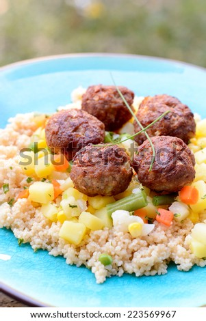 Meat balls with couscous and vegetables in the plate,selective focus - stock photo