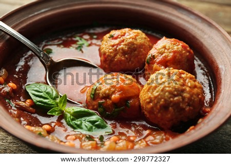Meat balls with tomato sauce and wooden spoon, close-up - stock photo
