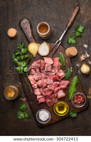 meat, cut into cubes, fresh herbs and spices on a cutting board on a dark wooden background top view - stock photo