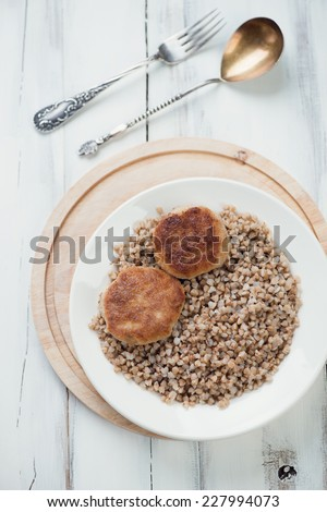 Meat cutlets and buckwheat in a plate, view from above - stock photo