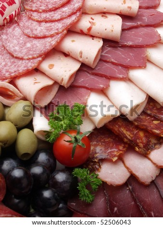 meat delicatessen plate arranged with cherry tomato, black and green olives and parsley - stock photo