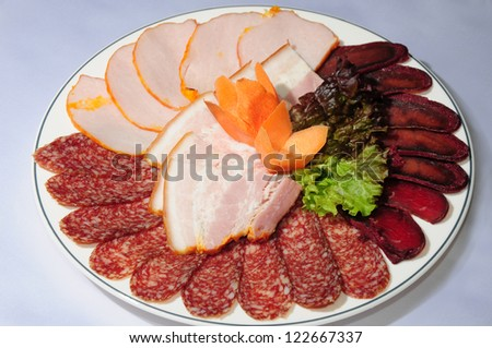 Meat delicatessen plate on banquet table - stock photo