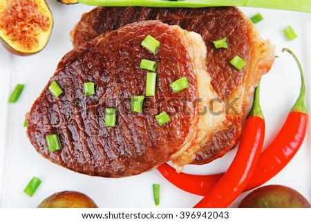 meat entree : grilled beef steak served with red hot cayenne peppers green chives and sweet figs on plate isolated over white background - stock photo