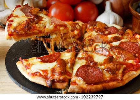 Meat feast Barbecue pizza with a topping of pepperoni, sausage, salami and chicken wings - stock photo