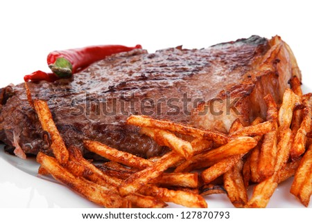 meat food : grill beef steak with potato chips and dry red hot chili peppers  on white round plate isolated on white background - stock photo