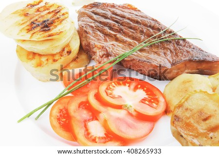 meat food : roast beef fillet steak served on white plate with tomatoes , potatoes , and chives isolated over white background - stock photo