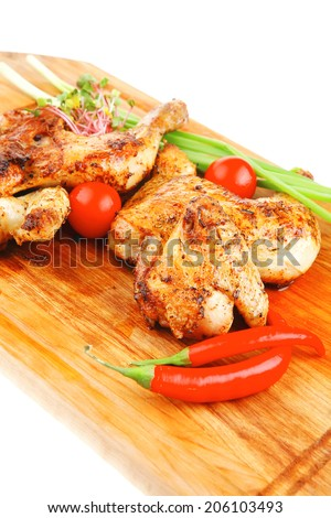 meat food : roasted chicken legs garnished with green sprouts and peppers on wooden plate isolated over white background - stock photo