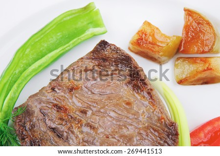 meat food : roasted fillet mignon on white plate with tomatoes apples and chili pepper over wooden table - stock photo