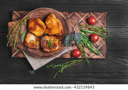 Meat fried pork steak baked, fresh green basil spices, thyme, rosemary, cherry tomatoes, burlap, brown dark wooden background in rustic style, top view - stock photo