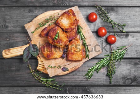 Meat fried pork steak baked, fresh green basil spices, thyme, rosemary, cherry tomatoes, gray dark wooden background in rustic style, top view - stock photo