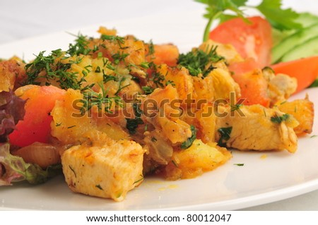 Meat fried with a potato on a white plate - stock photo