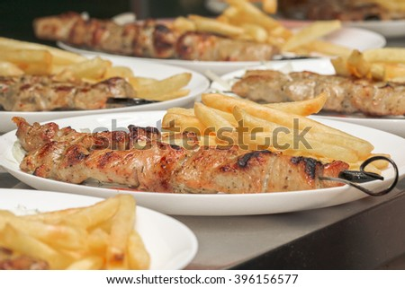 meat grilled on skewers with fries, a lot of servings. Greek cuisine. souvlaki - stock photo