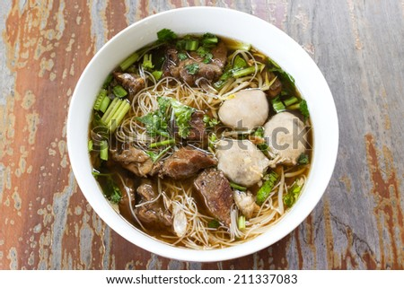 Meat Noodle in a bowl on wooden background. Thai Noodle small line with beef and meat ball. Favorite meal for lunch. Thailand food. - stock photo