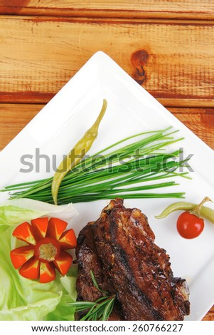 meat plate over wooden table: grilled ribs on white plate with red hot peppers, tomatoes and chives - stock photo