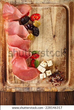 meat platter of Cured Meat and olives on old wooden board - stock photo