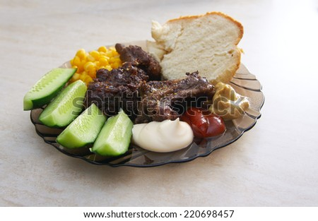 Meat roasted prime rib, fresh cucumbers, corn and homemade bread on a plate on the table - stock photo