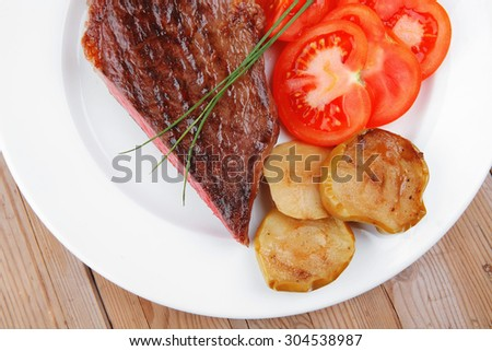meat savory : grilled beef fillet mignon served on white plate with tomatoes and potatoes on wooden table - stock photo