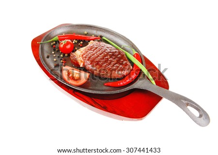 meat savory : platter of grilled beefsteak served with hot cayenne peppers red tomato green chives on metal pan isolated over white background - stock photo