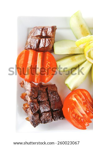 meat served with vegetables on white dish - stock photo