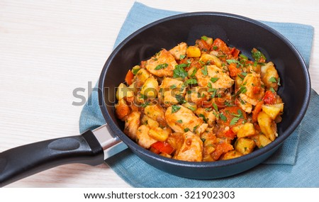 meat stew with potatoes, pepper, onion and carrot in a frying pan - stock photo