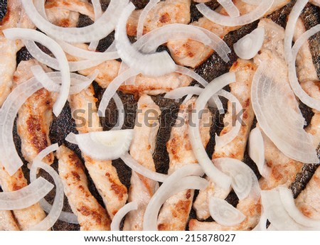 Meat Strips Fried With Onion In A Black Pan - stock photo