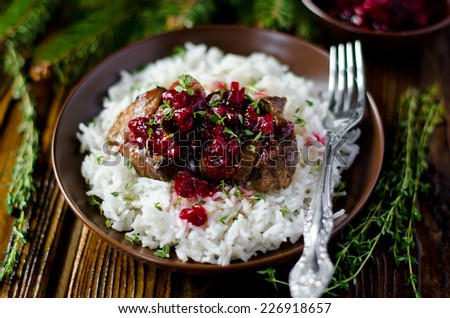 Meat with cranberry sauce and garnished with rice - stock photo