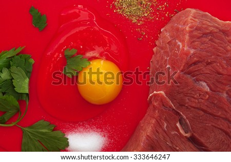 meat with egg yolk over red background - stock photo