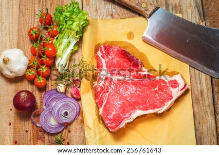 Meat with fresh vegetables, spices and meat cleaver on a wooden table vintage - stock photo