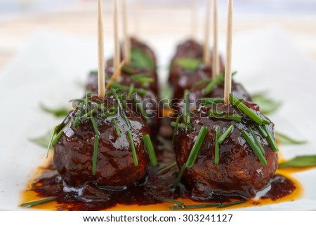 Meatball snacks with dark barbecue sauce on dish , garnished with chive - stock photo