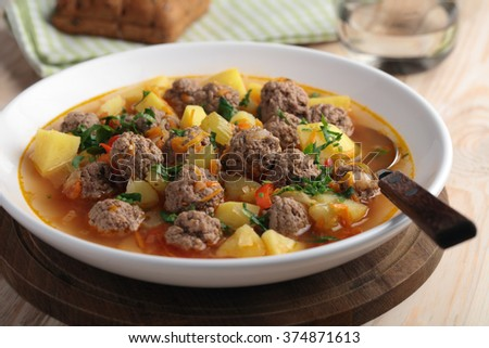 Meatball soup on a rustic table - stock photo