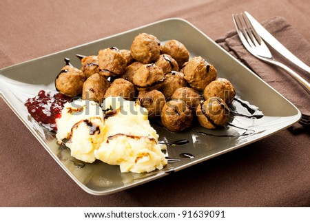 meatballs and mashed potatoes puree served in a green modern plate with oregano and vinegar garnish - stock photo