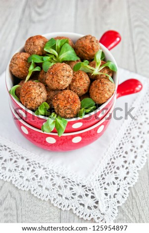 Meatballs and salad in a red bowl - stock photo