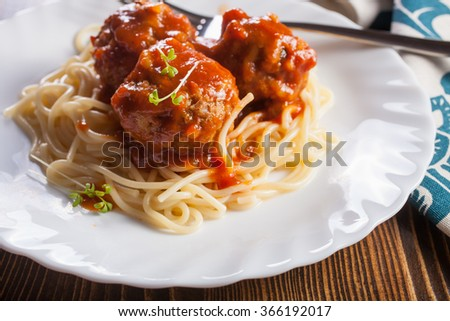 meatballs in tomato sauce from spaghetti in a plate on a table, selective focus - stock photo