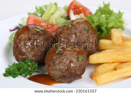 Meatballs meal with french fries and lettuce on plate - stock photo