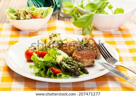 Meatballs served with boiled potatoes and asparagus on a plate - stock photo