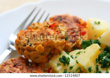 Meatballs with potatoes on a plate with a fork - stock photo