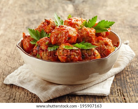 Meatballs with tomato sauce in a bowl on wooden table - stock photo