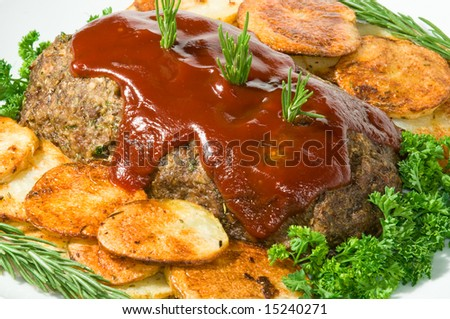 Meatloaf with fresh herbs, tomato sauce, and pan fried potatoes on white serving platter. - stock photo