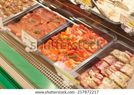 Meats in marinade on supermarket display, pre-cooked food - stock photo