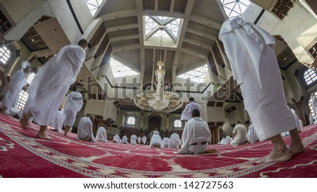 MECCA - FEB 25 : Muslim pilgrims in 'ihram' clothes pray at Tanaem mosque on Feb 25, 2012 in Mecca. 'Ihram' clothes consist of two unhemmed white clothes intended to make everyone appear the same. - stock photo