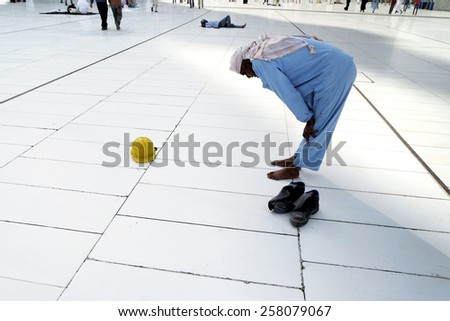 MECCA, SAUDI ARABIA - FAB 5: Praying outside kaaba, Muslim workers on Fabruary 5, 2015 in Mecca, Saudi Arabia. Muslims all around the world face the Kaaba during prayer time. - stock photo