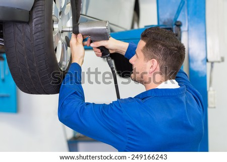 Mechanic adjusting the tire wheel at the repair garage - stock photo