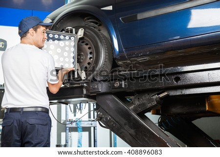 Mechanic Adjusting Wheel Aligner On Car - stock photo