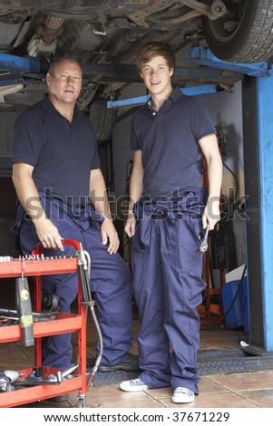 Mechanic and apprentice working on car - stock photo