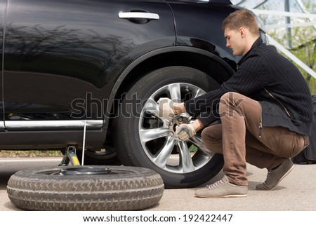 Mechanic changing a wheel during a roadside assistance call out to assist a driver in an emergency following a puncture - stock photo
