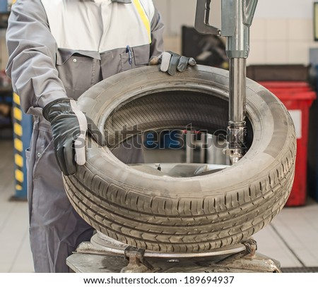 Mechanic changing car tire with bead breaker tool. - stock photo