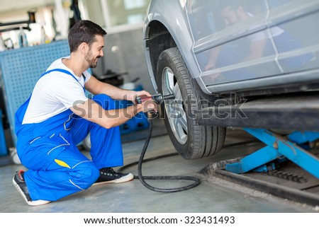 Mechanic changing tyre on car with air wrench in workshop - stock photo
