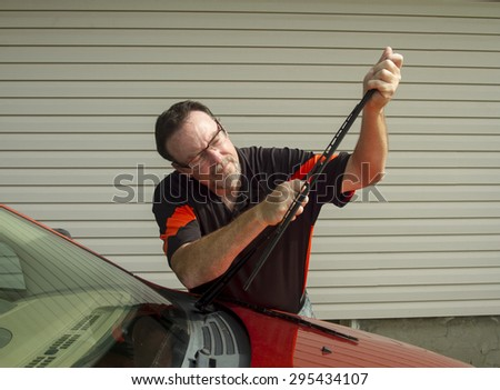 Mechanic changing windshield wiper blades on a car. - stock photo