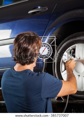 Mechanic Checking Gauge While Inflating Car Tire - stock photo