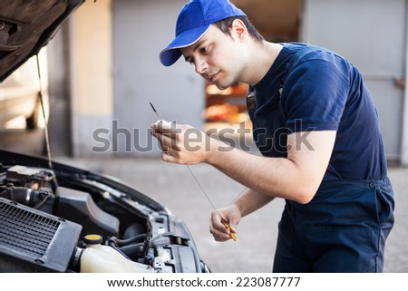 Mechanic checking the oil level in a car engine - stock photo